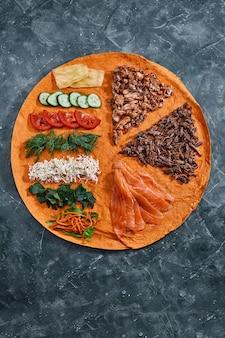 Hausgemachte döner, burrito, hühnchen und lachs brötchen mit gemüse und sauce. zutaten von oben mit freiem raum.
