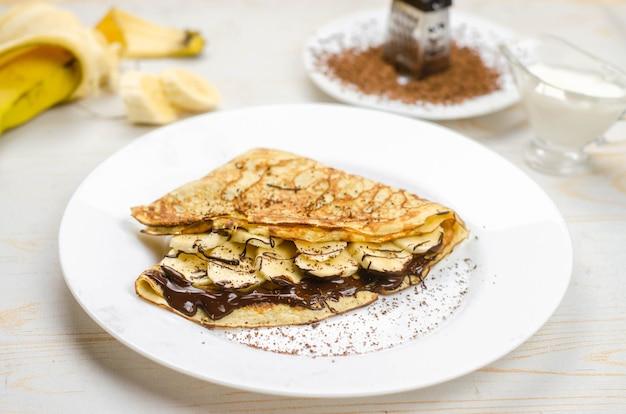 Hausgemachte dünne pfannkuchen mit hafermehl, banane, schokolade und nüssen