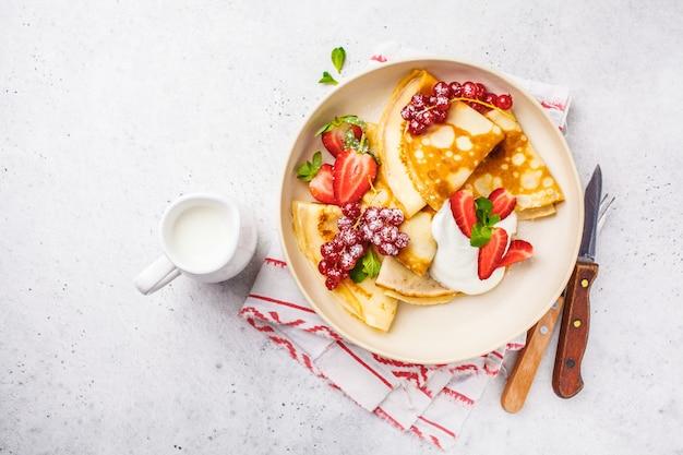Hausgemachte dünne pfannkuchen serviert mit quarkcreme