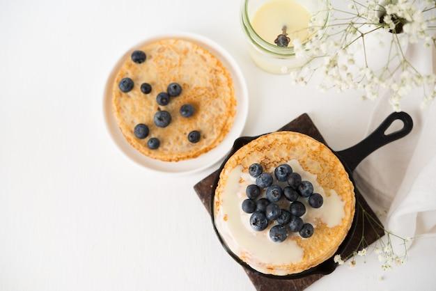 Hausgemachte dünne traditionelle pfannkuchen mit kondensmilch und blaubeeren, draufsicht, kopierraum