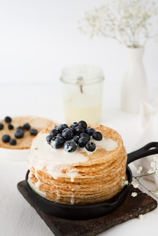 Hausgemachte dünne traditionelle pfannkuchen mit kondensmilch und blaubeeren, selektiver fokus, nahaufnahme
