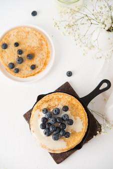 Hausgemachte dünne traditionelle pfannkuchen mit kondensmilch und blaubeeren