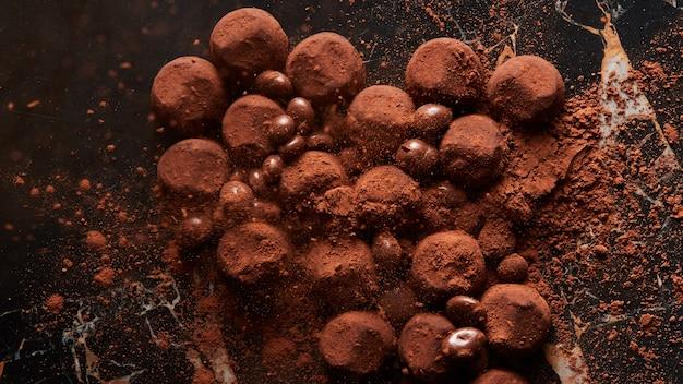 Hausgemachte dunkle schokoladentrüffel in verschüttetem kakaopulver auf dunkler marmoroberfläche. draufsicht,