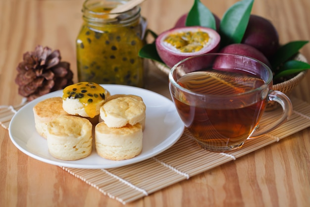 Hausgemachte einfache scones dienen mit maracuja marmelade und tee.