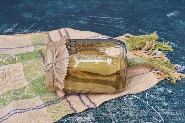 Hausgemachte eingelegte gurken im glas auf blau mit wolltischdecke.