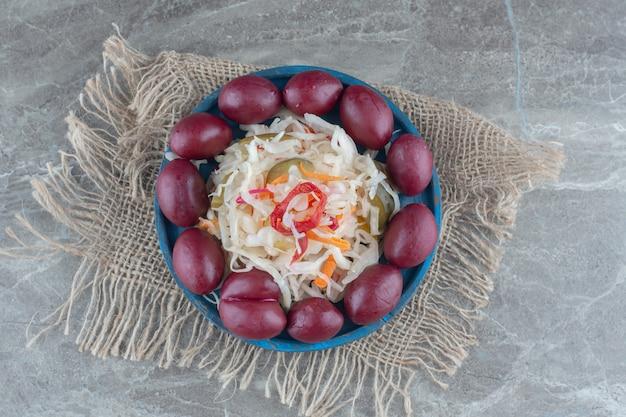 Hausgemachte eingelegte oliven und sauerkraut auf holzteller