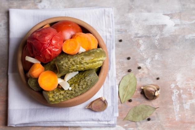 Hausgemachte eingelegte tomaten und gurken mit karotten, knoblauch und lorbeerblatt. leichte serviette.