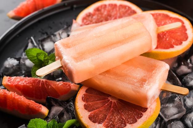 Hausgemachte eis am stiel der roten grapefruit mit eiswürfeln.