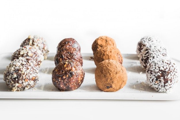 Hausgemachte energiebissen, vegane schokoladentrüffel mit kakao und kokosflocken. konzept gesundes essen.