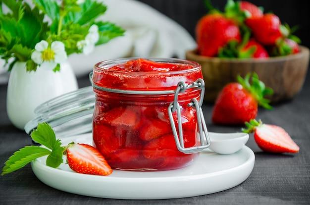 Hausgemachte erdbeermarmelade in einem glas mit frischen erdbeeren auf einem dunklen hölzernen hintergrund. rustikaler stil. horizontale ausrichtung.