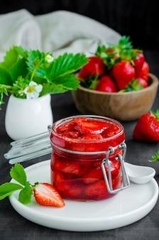 Hausgemachte erdbeermarmelade in einem glas mit frischen erdbeeren auf einem dunklen hölzernen hintergrund. rustikaler stil.