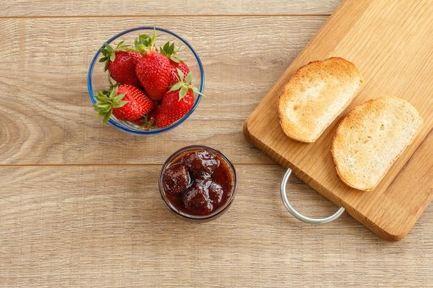 Hausgemachte erdbeermarmelade in einer glasschüssel, frische beeren, toast auf schneidebrett auf holzschreibtisch. ansicht von oben.