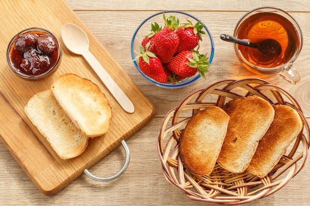 Hausgemachte erdbeermarmelade in einer glasschüssel, toast auf schneidebrett, frische beeren in schüssel, tasse tee und toast in einem weidenkorb auf holzhintergrund. ansicht von oben.