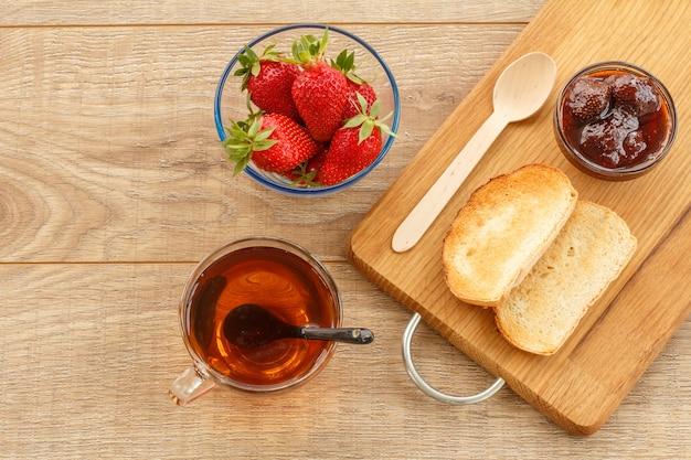 Hausgemachte erdbeermarmelade in einer glasschüssel und toast auf dem schneidebrett, frische beeren in der schüssel, eine tasse tee auf dem hölzernen hintergrund. ansicht von oben.