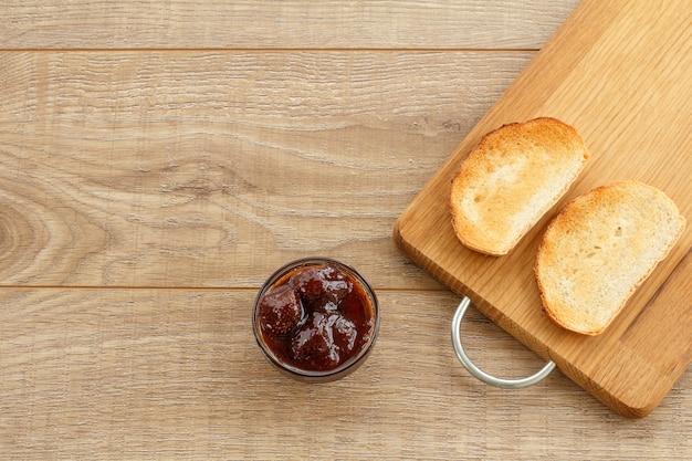 Hausgemachte erdbeermarmelade in einer glasschüssel und toast auf schneidebrett auf holzschreibtisch. ansicht von oben.
