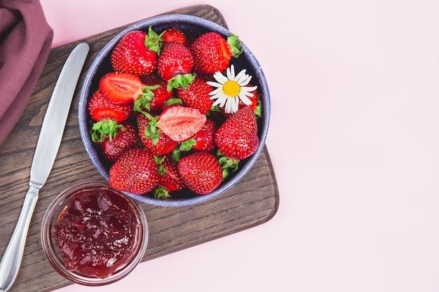 Hausgemachte erdbeermarmelade oder erdbeergelee mit frischen reifen erdbeeren auf einem weißen teller. frühstück mit brottoast mit erdbeermarmelade. messer zum streuen von marmelade. sommer bewahrt.