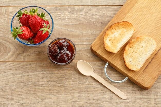 Hausgemachte erdbeermarmelade und frische beeren in glasschalen, toast auf schneidebrett mit löffel auf holzschreibtisch. ansicht von oben.