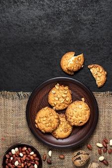 Hausgemachte erdnusskekse auf einem braunen teller mit rohen erdnüssen im hintergrund