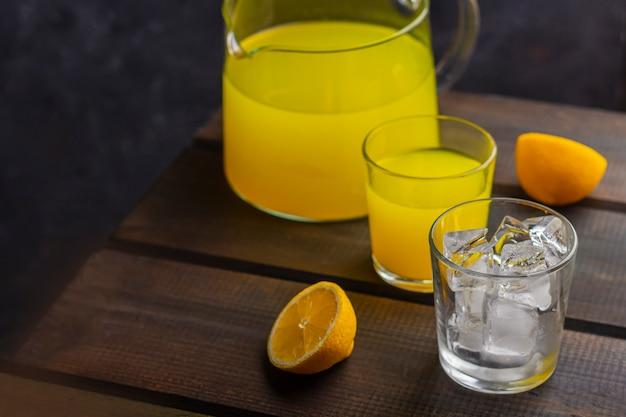 Hausgemachte erfrischende zitruslimonade im krug und im glas und glas mit eiswürfeln auf einem hölzernen hintergrund. frischer orangensaft. das konzept von bio-getränken und frischen vitaminen