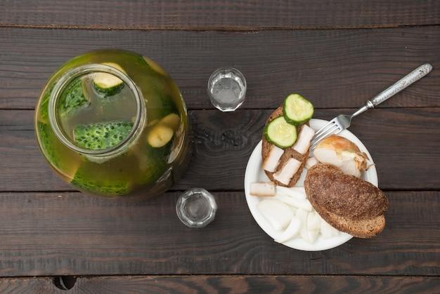Hausgemachte essiggurken mit gewürzen und kräutern in einem glasgefäß. zwei gläser und ein snack auf der oberfläche der dunklen bretter. ansicht von oben.