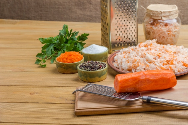 Hausgemachte fermentationsprodukte. rohe karotten, reibe und sauerkraut, petersilie und gewürze. gesunde winterernährung. helle holzoberfläche. speicherplatz kopieren
