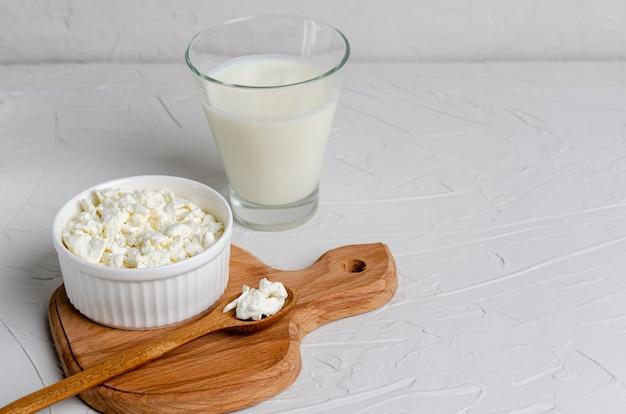 Hausgemachte fermentierte milchprodukte - kefir, hüttenkäse auf einem holzbrett