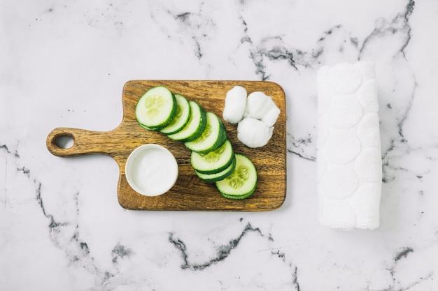 Hausgemachte feuchtigkeitscreme; gurkenscheiben und baumwolle auf schneidebrett mit handtuch über dem marmorhintergrund