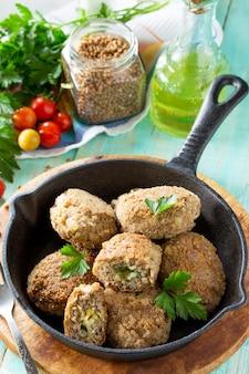 Hausgemachte fleischbällchen mit buchweizen- und eierfüllung castiron-pfanne mit köstlichen gebratenen schnitzel, frischen kräutern und gemüse auf dem küchentisch