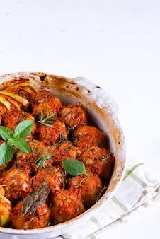 Hausgemachte fleischbällchen mit tomatensauce in einer weißen schüssel, die im ofen mit kräutern auf weißer marmoroberfläche gebacken wird Premium Fotos