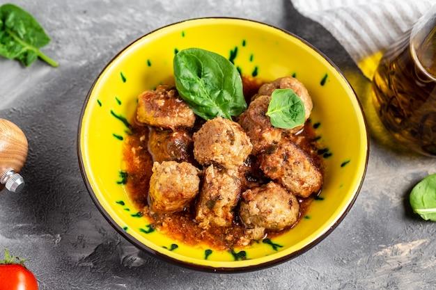 Hausgemachte fleischbällchen mit tomatensauce und gewürzen serviert in gelbem teller und grauer oberfläche