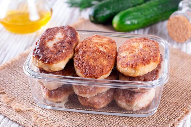 Hausgemachte fleischkoteletts in einem glasbehälter. gesundes essen
