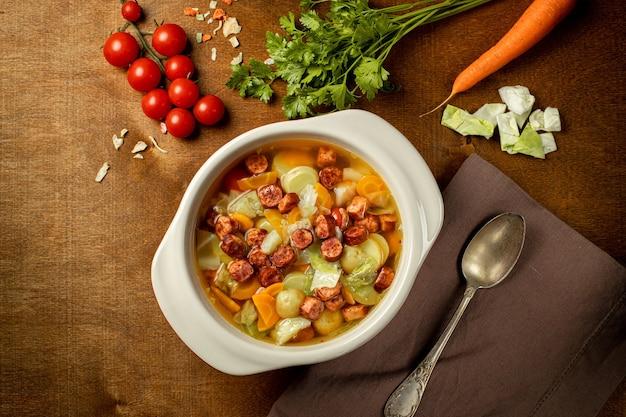 Hausgemachte frankfurter wurst in einem weißen suppenteller auf holzhintergrund. traditionelle kartoffelsuppe mit wurst. vertikale ausrichtung. ansicht von oben