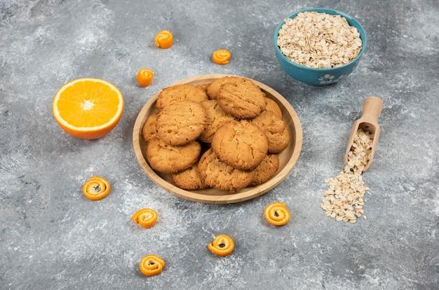 Hausgemachte frische kekse auf holzbrett und haferflocken mit orangen über grauer oberfläche.