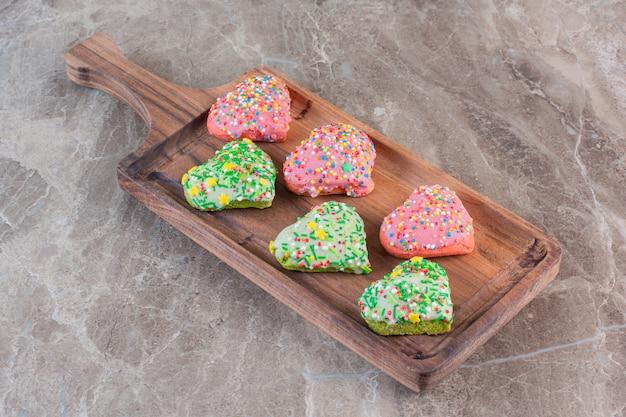 Hausgemachte frische kekse in hörbarer form auf holzbrett.