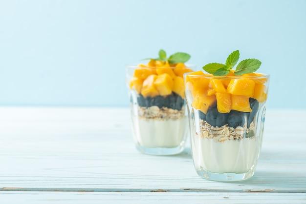 Hausgemachte frische mango und frische blaubeere mit joghurt und müsli. gesunde ernährung