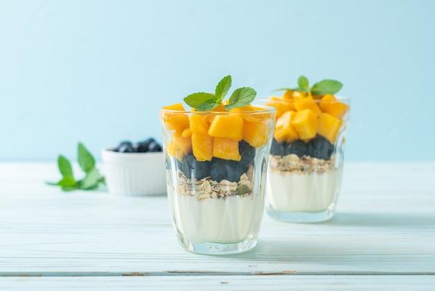 Hausgemachte frische mango und frische blaubeere mit joghurt und müsli - gesunde ernährung