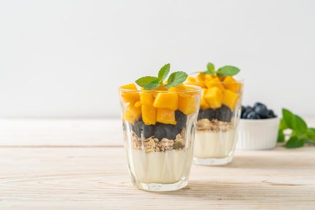 Hausgemachte frische mango und frische blaubeere mit joghurt und müsli