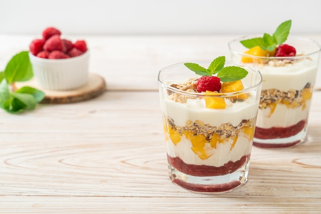Hausgemachte frische mango und frische himbeere mit joghurt und müsli. gesunde ernährung