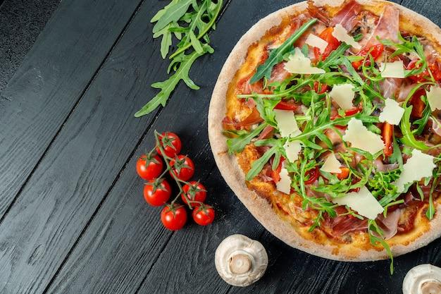 Hausgemachte frische pizza mit rucola, parmesan und kirschtomaten auf einem schwarzen holz mit kopierraum.