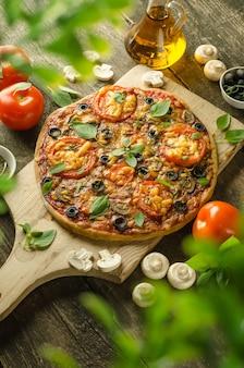 Hausgemachte frische vegetarische pizza mit käse und pilzen auf holzhintergrund und zutaten herum