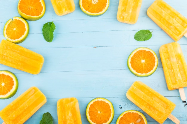 Hausgemachte frostige eis am stiel mit orangen auf einem blauen holz