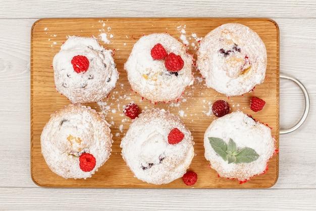Hausgemachte fruchtmuffins mit puderzucker und frischen himbeeren auf holzbrett bestreut. weihnachtsgebäck und süßigkeiten. ansicht von oben.