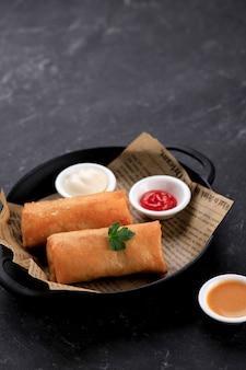 Hausgemachte frühlingsrolle, gefüllt mit hühnchen und garnelen, serviert mit saurer und süßer sauce. serviert auf schwarzem teller mit schwarzem hintergrund. platz für text kopieren