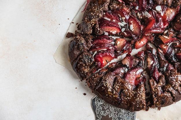 Hausgemachte galette oder offene torte mit schokolade, pflaume und mandel auf hellem betonhintergrund. ansicht von oben.