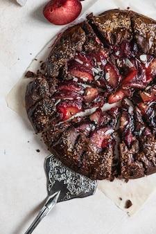Hausgemachte galette oder offene torte mit schokolade, pflaume und mandel auf hellem hintergrund. ansicht von oben.