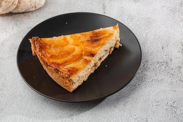 Hausgemachte gebackene apfelkuchen-torte mit äpfeln, die in einer dekorativen kreisförmigen form auf flockiger butterkruste auf marmorhintergrund geschnitten werden. rustikaler stil. speicherplatz kopieren. horizontal. menü für cafe