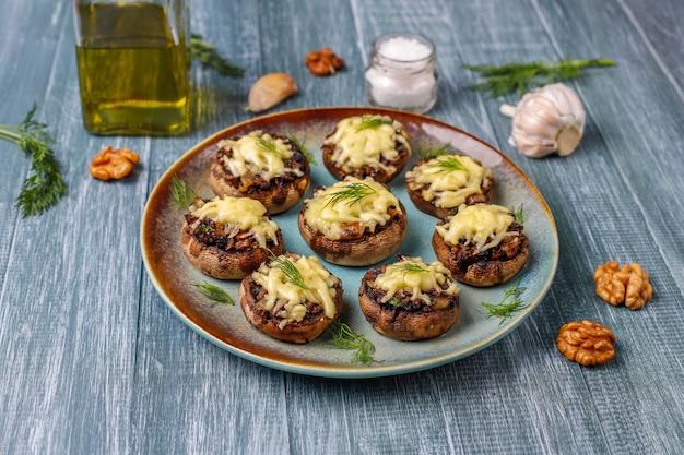 Hausgemachte gebackene gefüllte champignonpilze mit frischem dill und käse