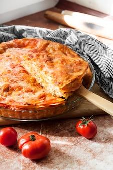 Hausgemachte gebackene lasagne in runder glasbackform auf holzbrett