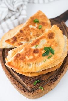Hausgemachte gebratene empanadas mit schweinefleisch, chebureks mit pilzen auf einem holzbrett, nahaufnahme