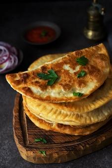 Hausgemachte gebratene empanadas mit schweinefleisch, chebureks mit pilzen auf einem holzbrett